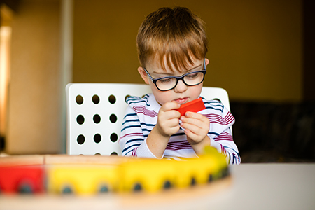 Kilkuletni chłopiec siedzi przy stole i bawi się drewnianym pociągiem