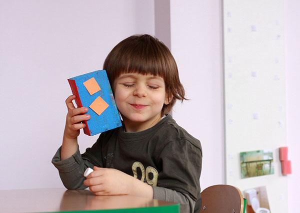 Kilkuletni chłopiec siedzi przy stoliku. Ma zamknięte oczy, jest uśmiechnięty, przykłada do ucha pudełko z kolorowego kartonu.